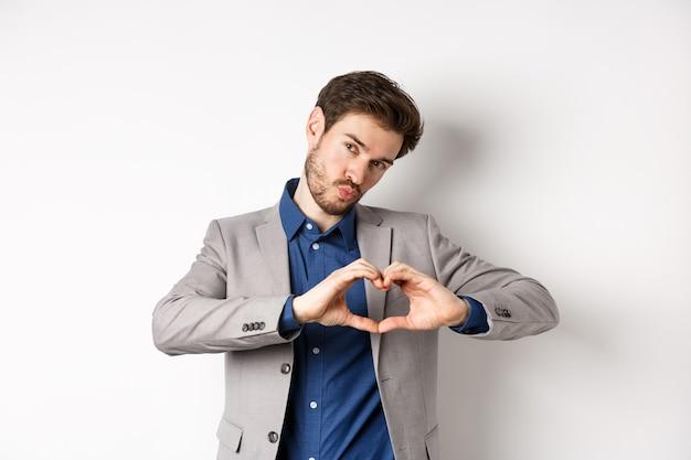 Romantische man in pak hart teken tonen en tuit lippen voor kus, liefde en passie uiten, zoals iemand, staande op een witte achtergrond.