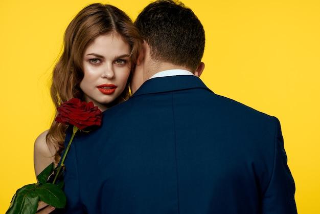 Romantische man knuffelt een vrouw in een rode jurk met een roos