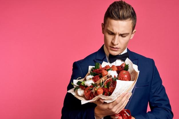 Romantische man met boeket bloemen en in vlinderdas op roze muur