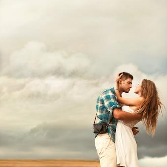 Romantische man omarmen zijn vriendin in de wei