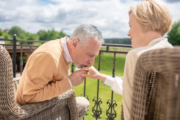 Romantische man van middelbare leeftijd die zijn liefde toont aan zijn vrouwelijke echtgenoot