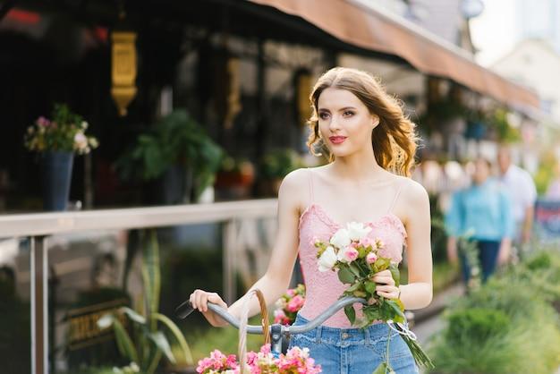 Romantische meisje staat en houdt een fiets met een mand met bloemen op een zonnige zomer