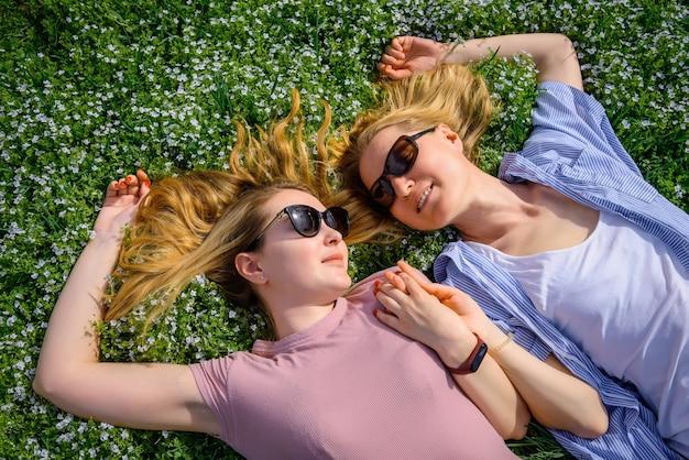 Romantische meisjes liggend op de bloeiende weide en hand in hand