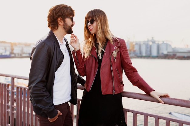 Romantische momenten van een stijlvol verliefd stel met een gesprek en genieten van de tijd die ze met elkaar doorbrengen. knappe man met zijn vrouw die op de brug loopt.