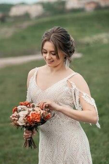 Romantische mooie bruid in luxe jurk poseren met bloemen in de buurt van de plaats van de huwelijksceremonie