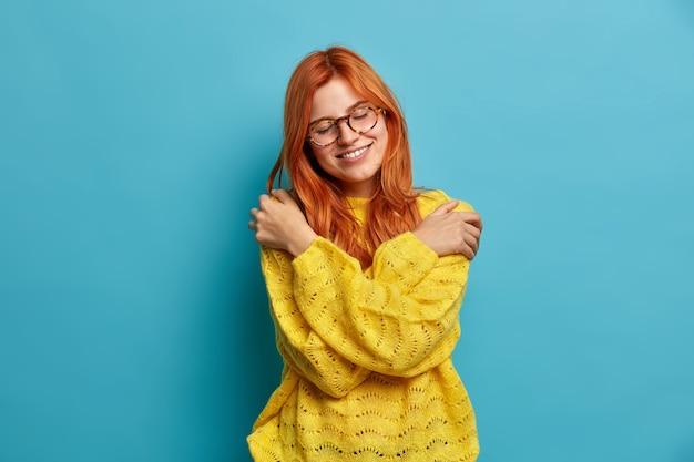 Romantische mooie roodharige vrouw omhelst zichzelf uitdrukt zelfliefde en zorg kantelt hoofd glimlacht zachtjes sluit ogen knuffels eigen lichaam draagt warme gele trui drukt kalmte uit.