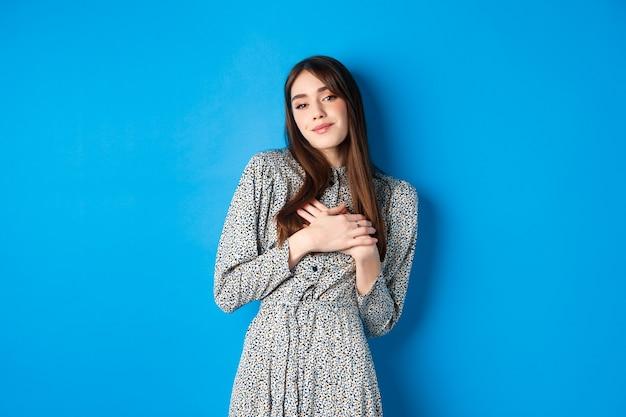 Romantische mooie vrouw in jurk hand in hand op hart, teder glimlachend, zoete herinneringen bewaren, staande op blauw.