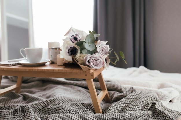Romantische ochtend. houten salontafel met bloemen op bed met plaid, koffiekopje, bloemen en kaarsen. lila rozen met eucalyptus en anemonen. grijze tinten interieur. hoge kwaliteit foto