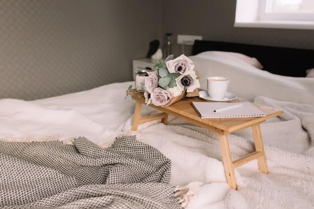 Romantische ochtend. houten salontafel met bloemen op bed met plaid, koffiekopje, bloemen en kaarsen, notitieblok, pen. lila rozen met eucalyptus en anemonen. grijze tinten interieur.