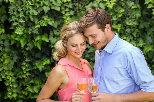 Romantische paar roosterende wijnglazen bij voortuin