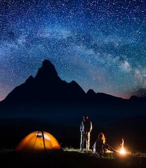 Romantische paartoeristen in zijn kamp bij nacht dichtbij kampvuur en tent tegen hooggebergteachtergrond en sterrige hemel