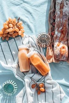 Romantische picknick aan zee. vers geperst sap, druiven en een vers frans stokbrood op een gestreepte deken, bovenaanzicht.