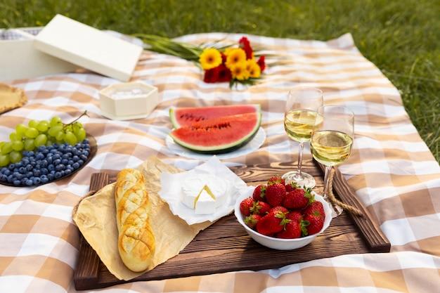 Romantische picknick in de natuur. de schoonheid van de ondergaande zon, vers fruit en wijn.