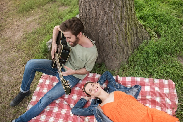 Romantische picknick. jonge, bebaarde man die gitaar speelt en een langharige vriendin die lacht terwijl hij op de deken rust onder de boom in de natuur