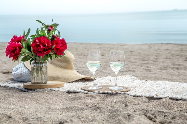 Romantische picknick met bloemen en glazen champagne aan zee. het concept van een vakantie.