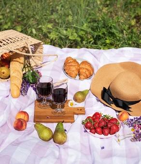 Romantische picknickscène op de zomerdag. outdoor picknick met wijn en fruit in de open lucht op de achtergrond van groen gras.