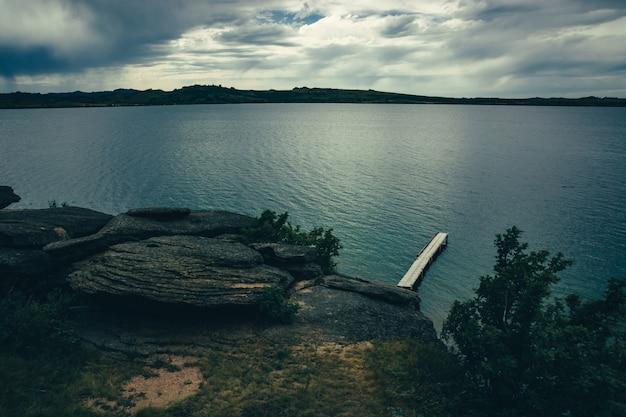 Romantische plaats op meer met houten pijler op rotsachtige kust