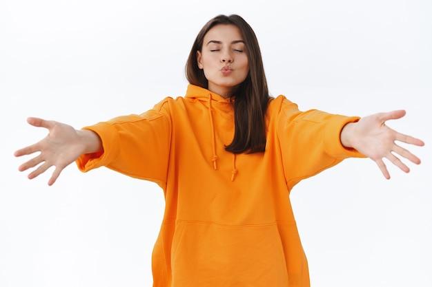 Romantische prachtige vriendin in oranje hoodie, sluit ogen en vouw lippen voor mwah, handen naar voren reikend om vriendje te knuffelen en te kussen, wil vriendin omhelzen, staande witte muur