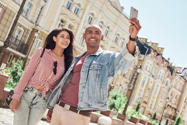 Romantische relatie jong divers koppel wandelen op de straat van de stad hand in hand nemen selfie