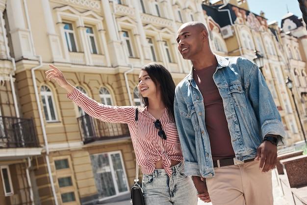 Romantische relatie jong divers stel wandelen op de straat van de stad hand in hand sightseeing
