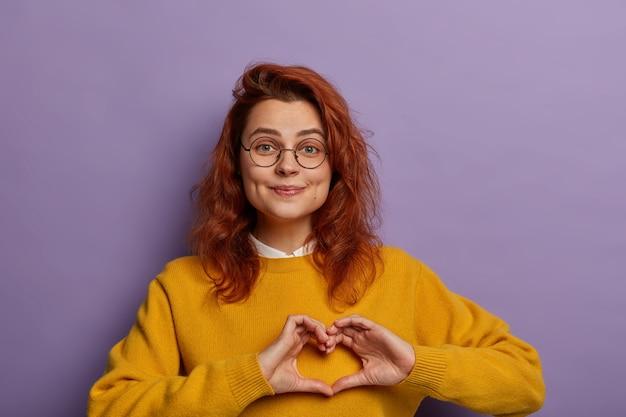 Romantische roodharige jonge vrouw toont hartgebaar over de borst, lacht aangenaam