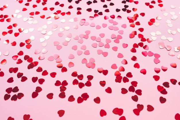 Romantische roze backround met rode folieharten