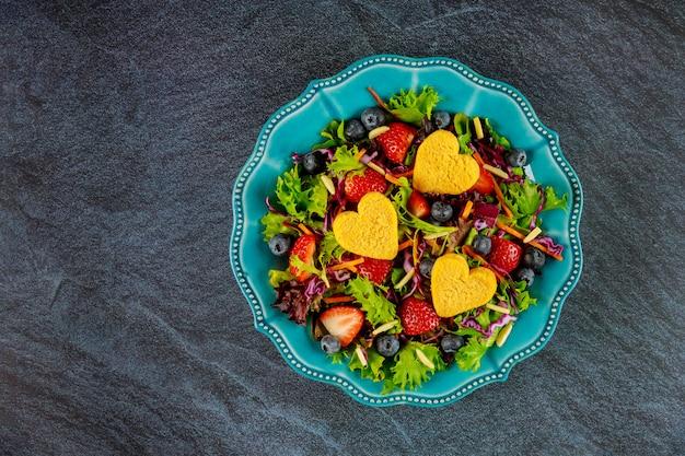 Romantische salade met sla, aardbeien, bosbessen en kipnuggets