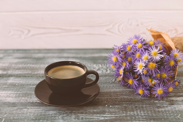 Romantische scène met een kopje koffie, een boeket van paarse bloemen in ambachtelijke papier op een grijze houten tafel