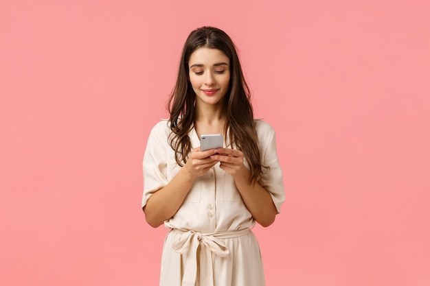 Romantische schattige, mooie jonge vrouw in jurk, chatten met vriendje, glimlachen, smartphone vasthouden en op het scherm tikken om online te bestellen, winkelen met toepassing