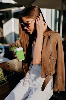 Romantische sensuele vrouw met een kopje koffie aan haar haar te raken heeft een goede tijd in de stad.