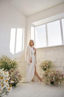 Romantische sexy vrouw in een jasje en een lange witte jurk staat in de buurt van het raam in kamillebloemen