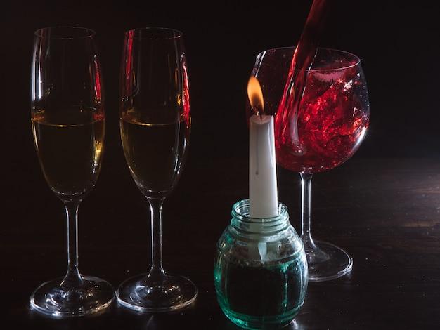 Romantische sfeer alcohol op zwarte achtergrond. rode wijn gieten in glas beweging reclame. liefdesdatum met de close-up van de kaarsachtergrond, romantiekconcept