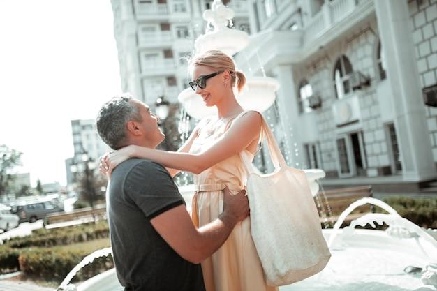 Romantische stemming. mooie blonde vrouw die lacht in de armen van haar man die met hem in de buurt van de fontein staat.