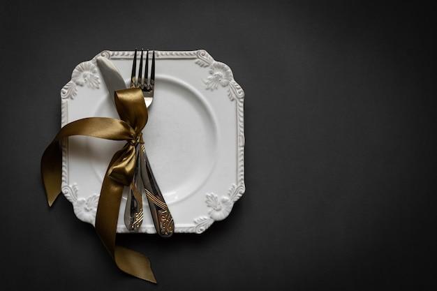 Romantische tafelomgeving met lint, borden, bestek op zwarte achtergrond. leeg bord. mockup design lay-out voor uw tekst. hou van romantisch concept. kopieer ruimte. bovenaanzicht. plat leggen.