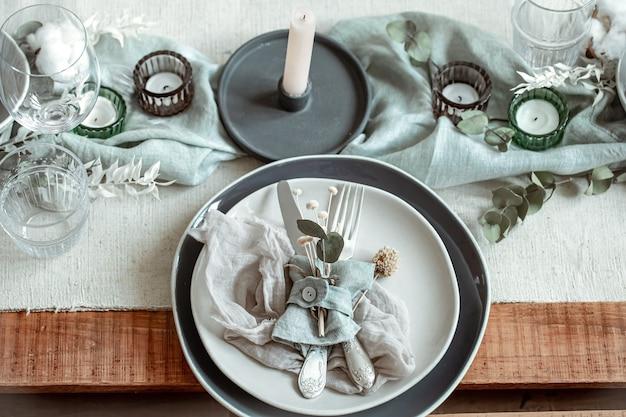 Romantische tafelsetting met brandende kaarsen en gedroogde bloemen met veel decoratieve details.