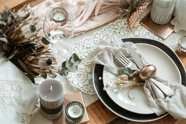 Romantische tafelsetting met brandende kaarsen en gedroogde bloemen voor de bruiloft met veel decoratieve details.