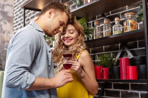 Romantische tijd. stralend gekrulde blonde vrouw glimlacht terwijl ze romantische tijd doorbrengt met haar man