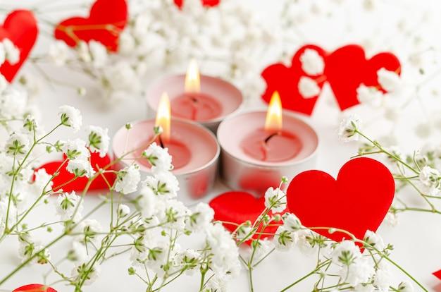 Romantische valentijnsdag. brandende kaarsen en rode harten versierd met bloemen op wit.