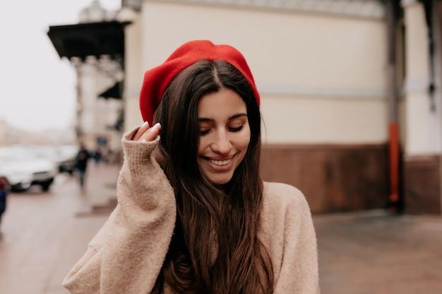 Romantische verlegen vrouw met lang donker haar, gekleed in een rode pet en een beige jas op straat