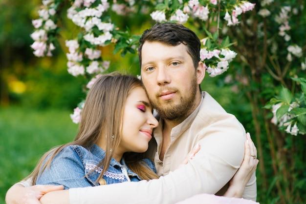 Romantische verliefde paar omarmen in het voorjaar in een bloeiende lila tuin