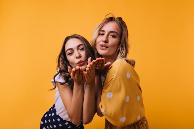 Romantische vriendinnen in trendy kleding staande op geel. zorgeloze meisjes die luchtkussen verzenden.