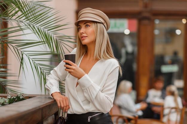 Romantische vrij blonde vrouw die van hete koffie buiten geniet