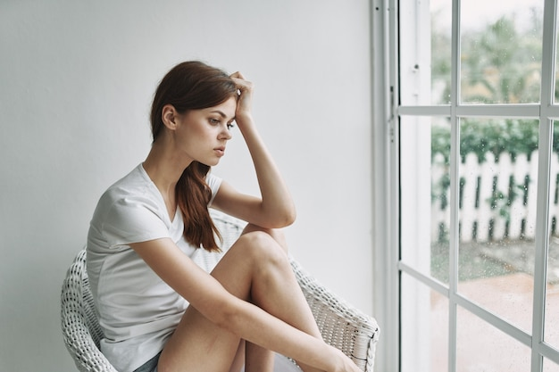 Romantische vrouw bij het raam zit in een stoel binnenshuis
