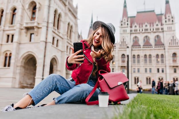 Romantische vrouw die in retro jeans op de grond zit en videogesprek gebruikt om te praten