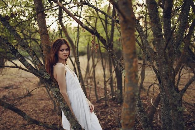 Romantische vrouw in de natuur in de buurt van bomen in het bos