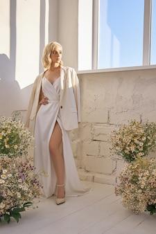 Romantische vrouw in een jasje en een lange witte jurk staat in de buurt van het raam in kamillebloemen