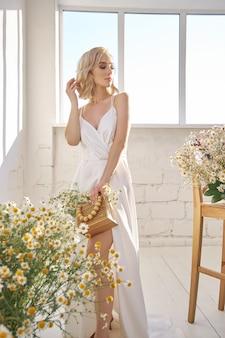 Romantische vrouw in een lange witte trouwjurk staat in de buurt van het raam in kamillebloemen