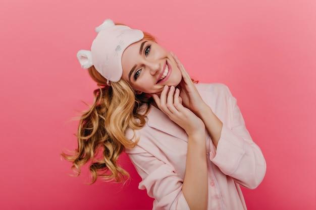 Romantische vrouw in elegante zijden pyjama met plezier in de ochtend. overweldigend kaukasisch meisje dat geluk op roze muur uitdrukt.