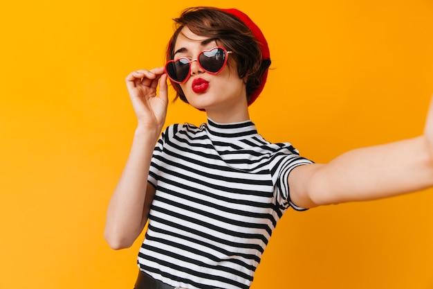 Romantische vrouw in hartvormige bril selfie te nemen