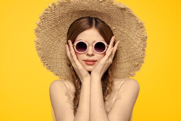 Romantische vrouw in hoed die pret op een gele achtergrond met modelportret van het zonnebril het zwarte lint heeft.
